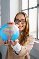 selbstbewusste frau mit brille hält einen globus in den händen