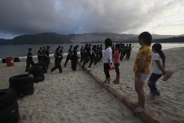 Bodyguard trainees run past by children during a training session in Sanya, Hainan province
