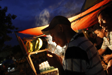 A man lights a cigarette after breaking his fast in front of a roadside tea stall in Dhaka