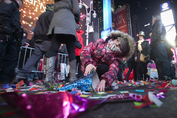 Maya Grace Hubbert plays with the confetti on 7th Avenue in Times Square on New Year's Eve in New York