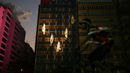 A US fan rides a bicycle past a building that has pictures of swimmers glued on the windows in Rio