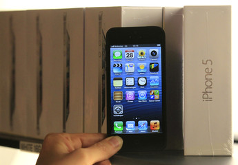 A customer holds up an Apple iPhone 5 to pose for a photo during an exclusive sale by Belgian operator Mobistar in Brussels