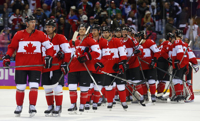 Team Canada players line up to shake hands with Team USA after Canada won their men's ice hockey semi-final game at the 2014 Sochi Winter Olympic Games