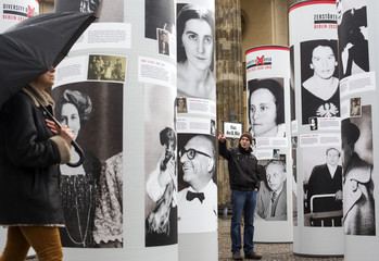 People look at the exhibition Diversity Destroyed in front of Brandenburg Gate in Berlin
