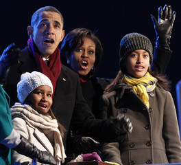 Obama and his family react as Sasha pushes the button to light the National Christmas Tree during a ceremony on the Ellipse in Washington