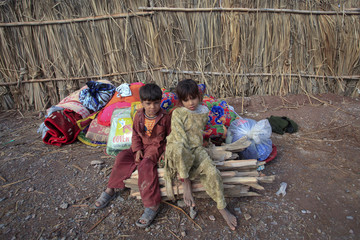 Internally displaced siblings sit on their family's belongings at the United Nations High Commission for Refugees-supported Jalozai camp in Khyber-Pakhtunkhwa Province