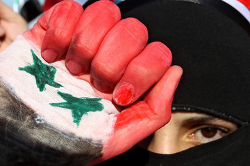 Syrian woman living in Jordan holds up her hand, painted with the Syrian national flag, and shout slogans in Amman