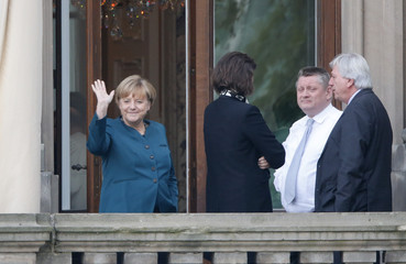 German Chancellor Merkel waves from a balcony while taking break during preliminary coalition talks in Berlin