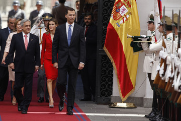 Spain's Crown Prince Felipe, his wife Princess Letizia, Chile's President Pinera and his wife Cecilia walk past an honour guard in Santiago