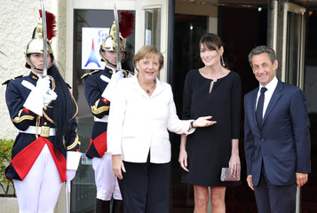 German Chancellor Merkel stands with France's First Lady Carla Bruni-Sarkozy and French President Sarkozy before a working dinner during the G8 summit in Deauville