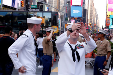 U.S. Navy sailors stop to take photographs as they walk through Times Square during Fleet Week in New York