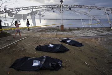 A woman takes pictures next to remains of victims of Typhoon Haiyan in body bags, at Tacloban