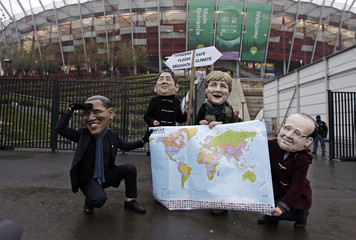 Protesters wearing masks of world leaders hold a map and a sign on the last day of U.N. climate talks in Warsaw