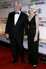 Former House speaker and Republican presidential nominee hopeful Newt Gingrich and his wife Callista pose for photographers on the red carpet as they arrive to the Kennedy Center for the gala performance for the 2011 Kennedy Center Honorees in Washington