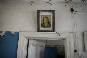 A portrait is seen in a house in the abandoned village of Zalesye near the Chernobyl nuclear power plant