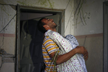 A Palestinian man reacts as he hugs his mother after his house was damaged in an Israeli air strike in Gaza
