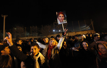 A Kurdish woman holds up a picture of PKK co-founder Cansiz, one of the three Kurdish activists shot dead in Paris, while waiting for the ambulances carrying their bodies in Diyarbakir