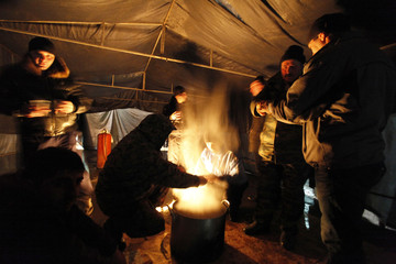 Supporters of South Ossetian Presidential candidate Alla Dzhioyeva warm themselves near a fire inside a tent during a rally in the central square in Tskhinvali