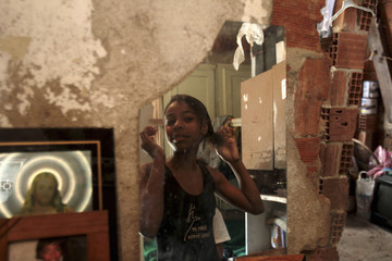 Marie Ellen da Silva fixes her hair in her home, before going to her ballet classes, in Santa Teresa neighborhood in Rio de Janeiro