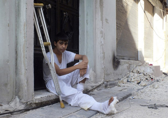 A man sits in front of his house after receiving medical aid in Homs