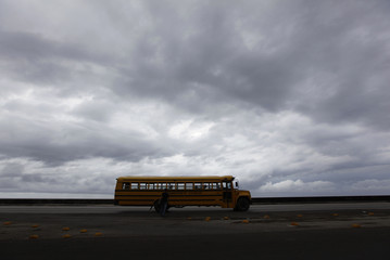 """A school bus travels along Havana's seafront boulevard """"el Malecon"""", as storm clouds gather in the sky"""