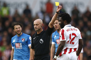 Referee Roger East shows a yellow card to Stoke City's Wilfried Bony