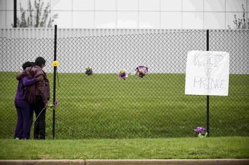 U.S. music superstar Prince fan Mona Shelton hugs an unidentified employee as she places flowers outside of Paisley Park in Chanhassen Minnesota