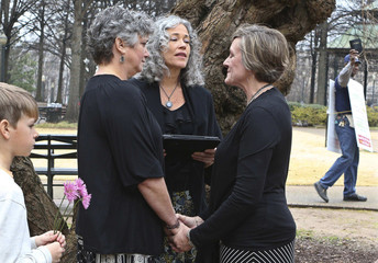 A protester waving a bible walks past in the background as two women named Donna and Tina get married in a park outside the Jefferson County Courthouse in Birmingham