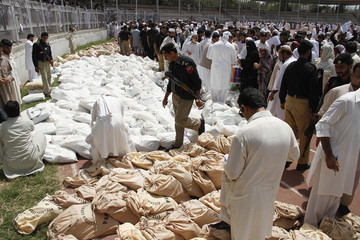 Election workers and policemen stand around sacks containing stationery before transporting them to polling stations, at a sport complex used as a storage area for election material in Peshawar