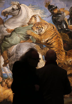 """Visitors look at """"Tiger, Lion and Leopard Hunt"""" from 1617 by Peter Paul Rubens at an exhibition in London"""