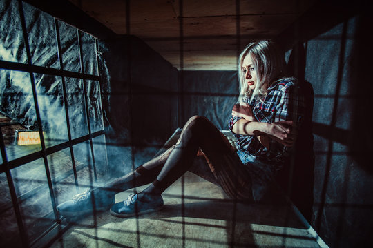Frightened blond woman in the dark cage.