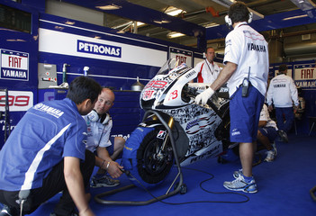 Pit crew members go over the motorcycle of Yamaha MotoGP rider Jorge Lorenzo of Spain during the first practice round of the U.S. Grand Prix at Laguna Seca Raceway in Monterey