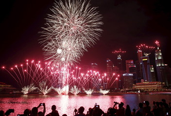 People take photos of fireworks in the skyline of Singapore during a National Day Golden Jubilee parade rehearsal