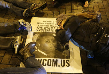 Demonstrators lie down in the middle of the street in protest following the grand jury decision in the Ferguson, Missouri shooting of Michael Brown, in Seattle, Washington