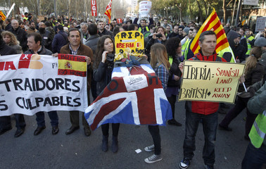Iberia workers hold banners as they protest outside the Iberia headquarters in Barcelona