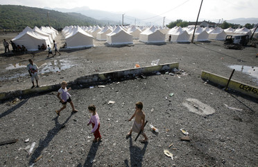 Roma children, refugees from Kosovo, play at the remains of a playground at the refugee camp Vrela Ribnicka in Podgorica