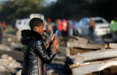 A woman uses her phone to take pictures of the wreckages of cars burnt after a fireball from an tanker engulfed several vehicles and killed several people, near the Rift Valley town of Naivasha, west of Kenya's capital Nairobi