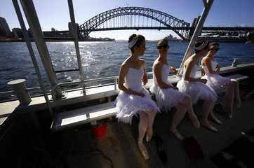 Ballerinas from The Australian Ballet sit on a boat after performing on a floating platform during a promotional event in front of the Sydney Opera House and Harbour Bridge