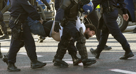 A man is removed by police during a protest against the NATO summit in Lisbon