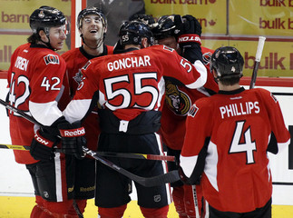 Ottawa Senators' Foligno watches the replay of his open-net goal as teammates O'Brien, Gonchar, Neil and Phillips celebrate during the third period of their NHL hockey game against the Washington Capitals in Ottawa