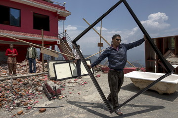 A worker carries a broken frame of window glass from a collapsed hotel after the April 25 earthquake in Sindhupalchowk