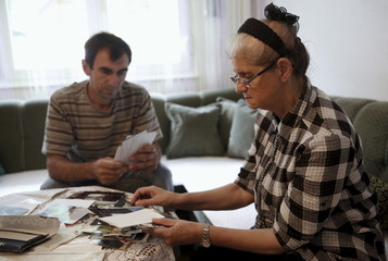 Catic and Jakubovic look at pictures of Hajra's son at her home in Srebrenica