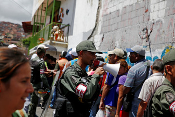 Venezuelan soldiers control the crowd as people queue trying to buy basic food during a special inspection to a municipal market in Caracas