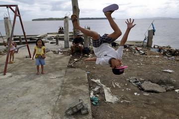 John Dave Galang, a survivor of Typhoon Haiyan, shows his acrobatic skills at a devastated area of Basey, north of Tacloban
