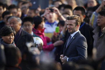 Former England soccer team captain Beckham unbuttons jacket before exhibition match with middle school students in Beijing