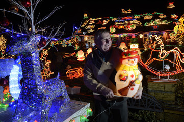 Eric Marshall sets up his Christmas lights on his house in Bagby