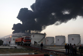 Firefighters and officials stand as smoke billows from Indian Oil Corporation's fuel depot in Hazira