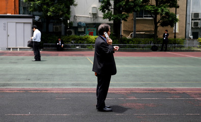 Businessmen use mobile phones at a park in a business district in Tokyo