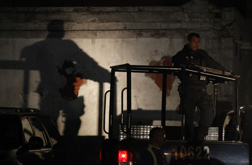 Federal policeman stands guard atop a patrol at the perimeter of a crime scene in downtown Monterrey