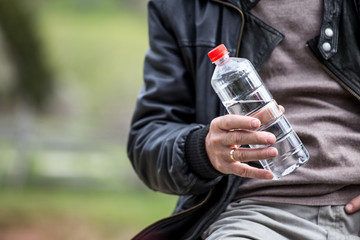 Closeup of bottle of water in man hand